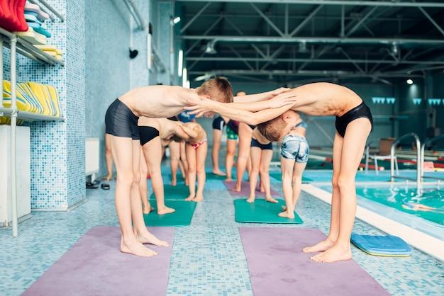 Garçons faisant des exercices sportifs par paires près de la piscine.