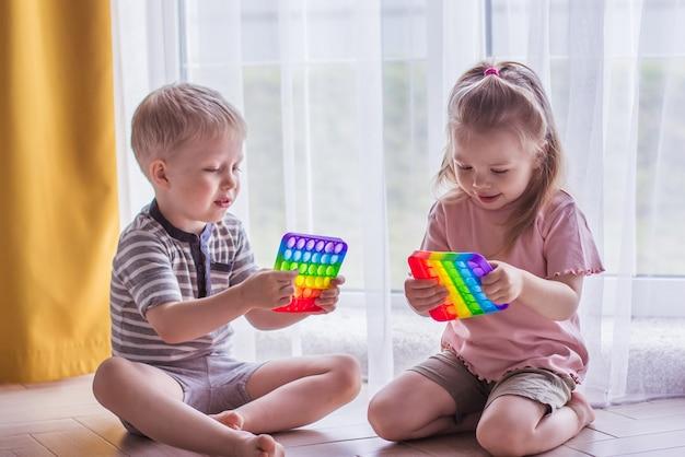 Des garçons et des filles blonds sont assis sur le sol près de la fenêtre et jouent à un jouet en silicone anti-stress. pop it jouet sensoriel. soulagement du stress. jouet coloré de capteurs de silicone anti-stress
