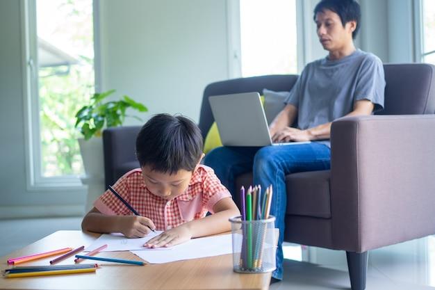 Les garçons font leurs devoirs à la maison. papa s'est assis sur le canapé et a enseigné les devoirs aux enfants.