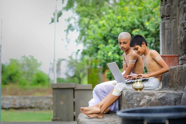 Garçons indiens apprenant sur ordinateur portable