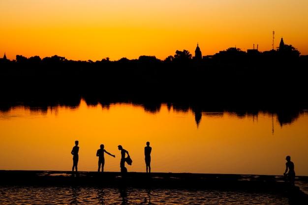 Garçons indiens indiens se lavant au bord du lac.