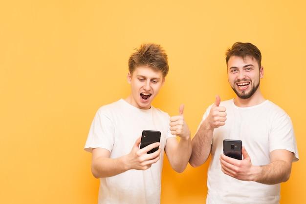 Garçons sur jaune utilisent un smartphone et sourient.
