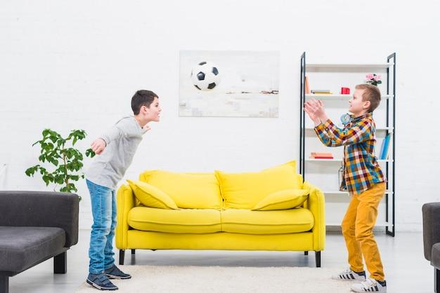 Garçons jouant au football dans le salon