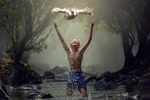 Garçons jouant avec leur canard dans la crique