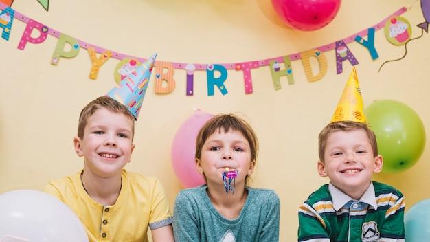 Garçons joyeux et fille sur la fête d'anniversaire