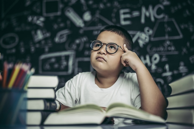 Les garçons avec des lunettes écrivent des livres et réfléchissent en classe