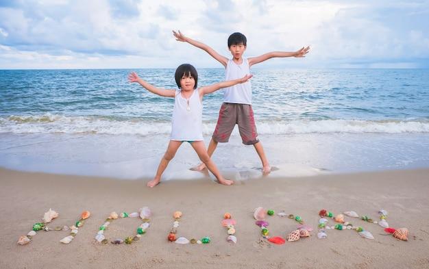 Les garçons mignons d'asie passent un bon temps sur la plage à la mer en vacances.
