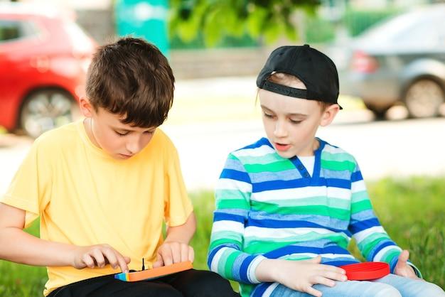 Garçons mignons jouant avec un jouet pop it à la mode. amis en promenade avec des jouets à bulles en silicone. les garçons s'amusent à l'extérieur. jouet anti-stress moderne pour enfants