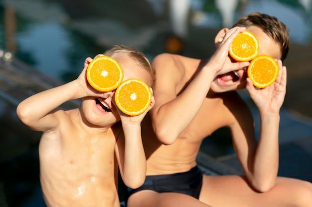 Garçons à la piscine avec orange