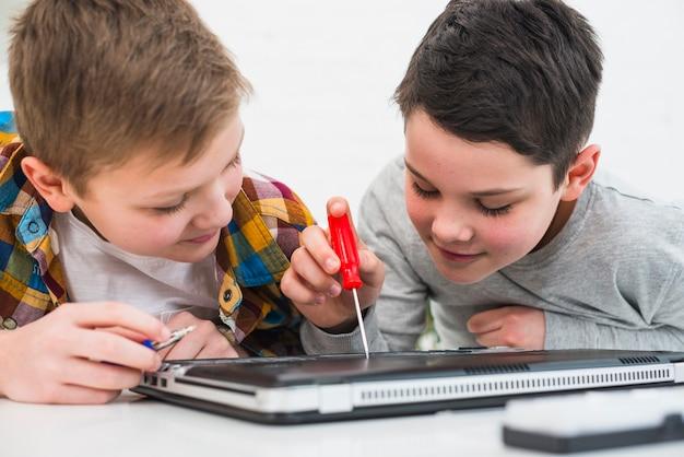 Garçons réparant un ordinateur portable