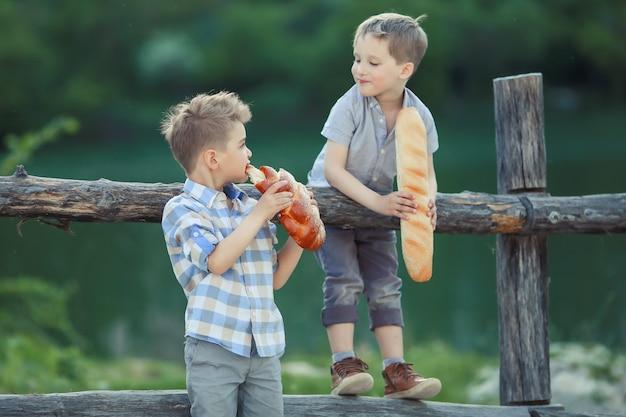 Un garçons se tiennent près d'une clôture en bois dans un willage