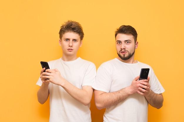 Les garçons sérieux en t-shirts blancs sont avec des smartphones dans leurs mains sur jaune