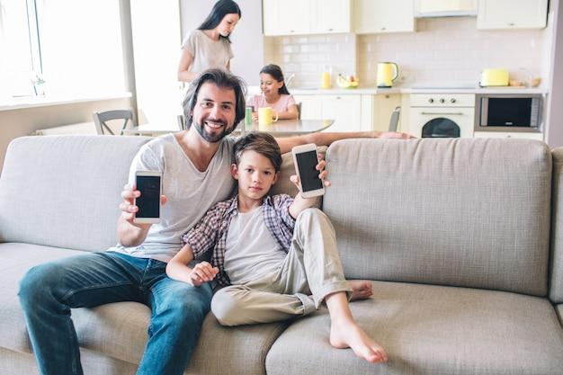 Les garçons sont assis sur le canapé et tient le téléphone dans les mains