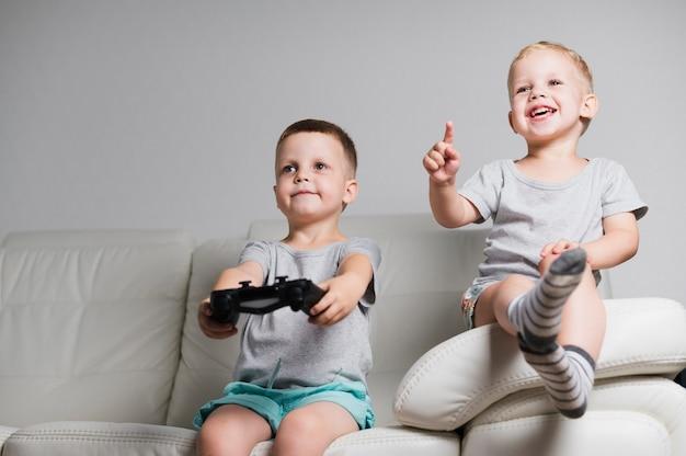 Garçons souriants vue de face jouant avec les contrôleurs