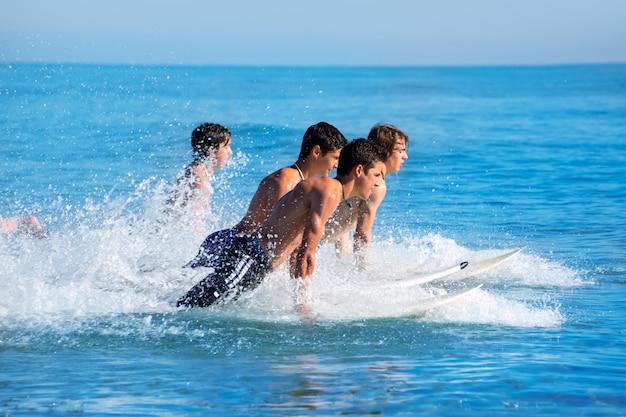 Garçons surfeurs surfant en cours d'exécution sautant sur des planches de surf