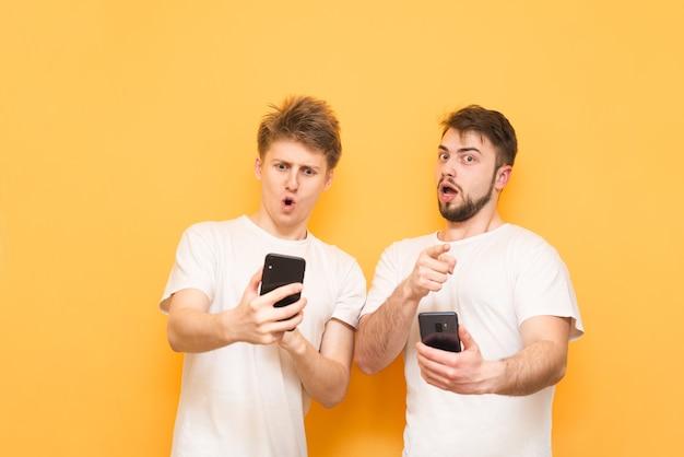 Garçons surpris avec des smartphones dans leurs mains