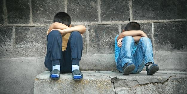Garçons tristes caucasiens assis dans la rue.