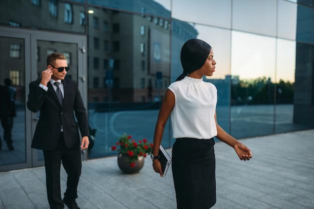 Garde du corps de femme d'affaires noir en costume et lunettes de soleil