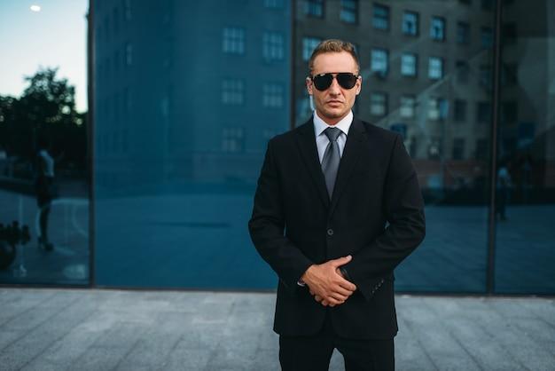 Garde du corps masculin en costume, écouteur de sécurité et lunettes de soleil à l'extérieur.