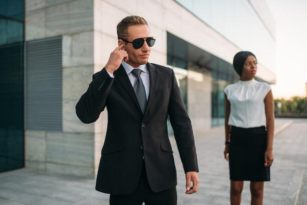 Garde du corps personnel en lunettes de soleil et femme d'affaires noire.