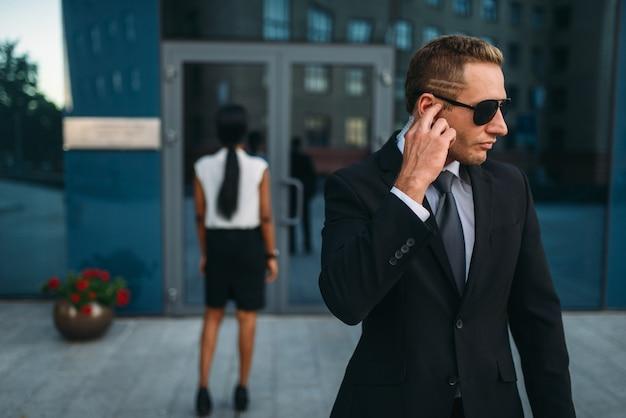 Garde du corps sérieux en costume et lunettes de soleil