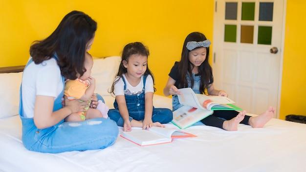 Garde d'enfants jouant avec trois enfants ludiques portant sur le lit