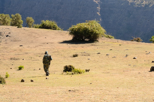 Garde forestier armé marchant dans le parc national du mont simien pendant la saison sèche, destination touristique en éthiopie
