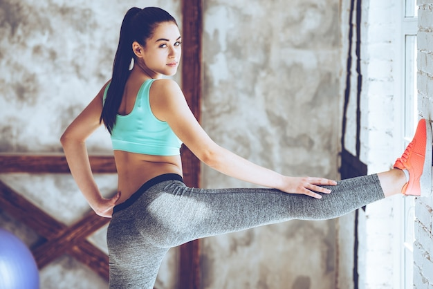 Garder ses jambes en pleine forme. belle jeune femme en tenue de sport étendant sa jambe et regardant la caméra tout en se penchant contre le mur au gymnase