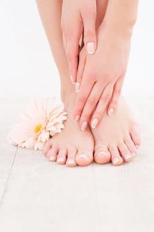 Garder ses pieds propres et lisses. gros plan d'une femme touchant ses pieds en se tenant debout sur un plancher de bois franc