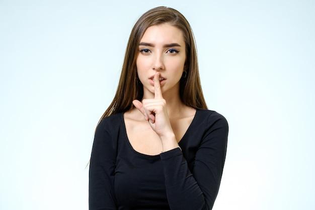 Garder le silence! belle jeune femme tenant le doigt sur les lèvres