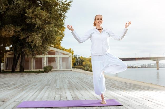 Garder son calme et son équilibre. la jeune femme est calme en faisant du yoga asana difficile