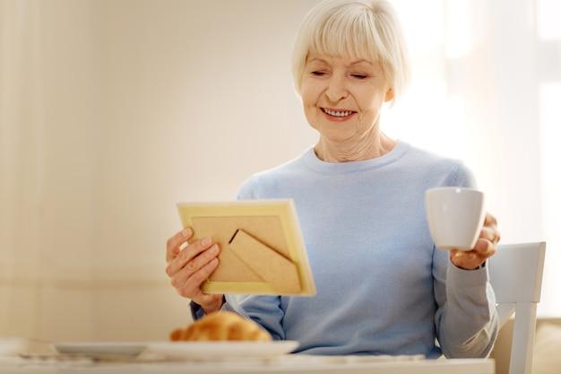 Garder le sourire. heureux positif retraité femme tenant tasse dans la main gauche et regardant vers le bas tout en étant à la maison