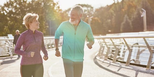 Gardez la forme joyeuse famille d'âge mûr couple actif en tenue de sport souriant les uns aux autres tout en