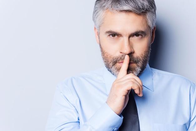 Gardez mon secret ! homme mûr confiant en chemise blanche et cravate regardant la caméra et tenant le doigt sur les lèvres en se tenant debout sur fond gris
