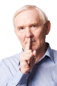 Gardez mon secret ! homme senior sérieux en chemise tenant le doigt sur les lèvres et regardant la caméra en se tenant debout sur fond blanc