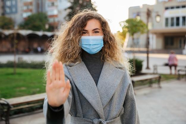 Gardez vos distances sociales. femme en masque de protection contre les virus montrant le geste arrêter l'infection. concept de pandémie et de soins de santé du coronavirus covid-19.