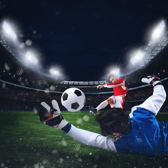 Le gardien attrape le ballon dans le stade lors d'un match de football