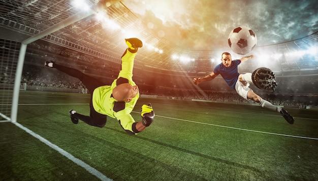 Le gardien de but attrape le ballon dans le stade lors d'un match de football