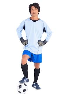 Gardien de but en bleu tenant le ballon avec le pied