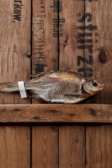 Gardon séché au soleil avec étiquette en papier sur la queue sur des planches en bois brut