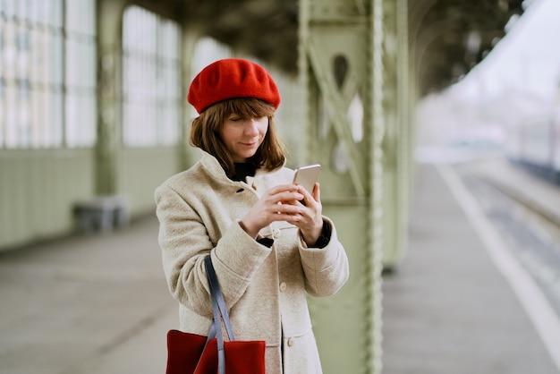 Gare. belle fille attend le train et regarde le téléphone portable