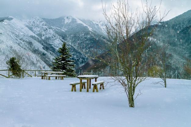 Garez-vous sans personne au point de vue de la montagne en hiver avec des vues spectaculaires au fond des montagnes enneigées des bancs en bois et des tables recouvertes d'une épaisse couche de neige