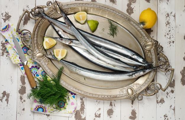 Garfish, poissons porte-épines crus et frais, vue de dessus, avec oignons, citron, préparés pour la cuisson