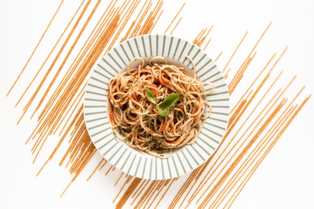 Garnir les pâtes spaghettis de pâtes crues sur une surface blanche