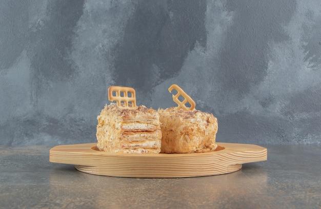 Garniture de biscuit sur des tranches de gâteau sur un plateau en bois