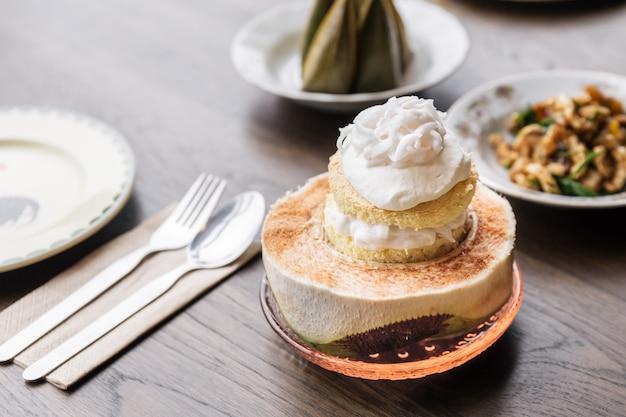 Garniture de gâteau à la crème glacée à la noix de coco avec de la viande de noix de coco qui sert dans une moitié de noix de coco dessert fusion thaï.