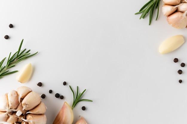 Garniture et ingrédients alimentaires poivre noir romarin gousses d'ail et morceaux d'ail cru