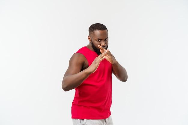 Un gars afro-américain adulte, drôle et ludique, debout de profil dans les arts martiaux pose avec les paumes levées, les sourcils froncés et le regard perdu.