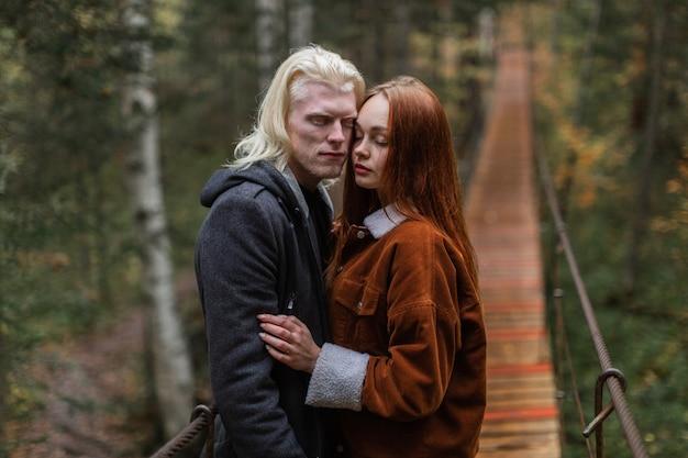 Un gars albinos et une fille rousse se tiennent sur un pont dans les bois et se câlinent les yeux fermés