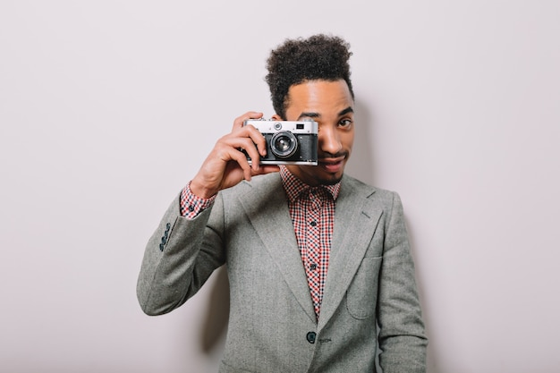 Gars américain-africain élégant moderne posant sur le mur blanc avec un appareil photo rétro et prend la prise de vue sur le gris